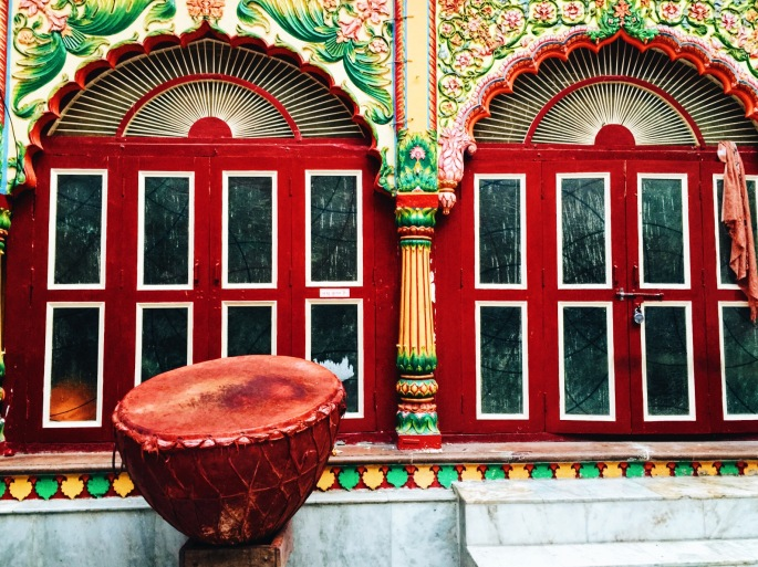 A huge drum, used in religious festivals, placed in front of a colored temple door in Mathura.
