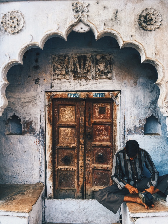 A traditional old door, with a man resting next to it.