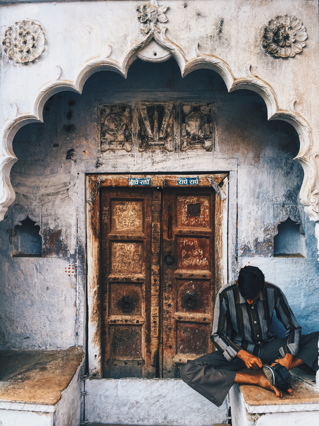 A traditional old door with a man resting next to it. & Doors Are Stories: The Photographic Obsession of Divyakshi Gupta ... pezcame.com