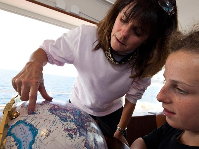 A teacher (and recipient of the organization's professional development program, the Grosvenor Teacher Fellowship) explores a globe.