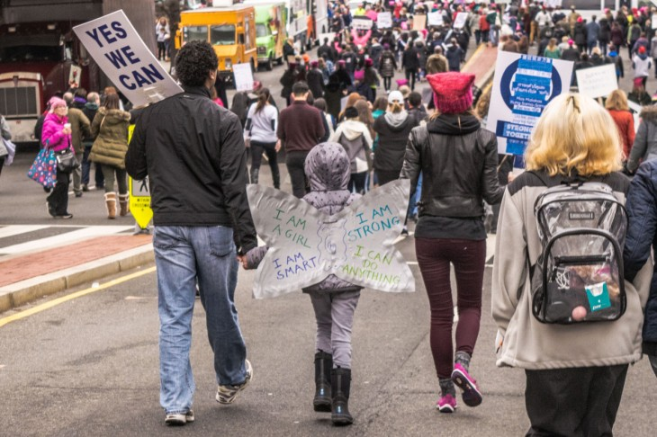 A young girl marches with her family at the Women's March on Washington