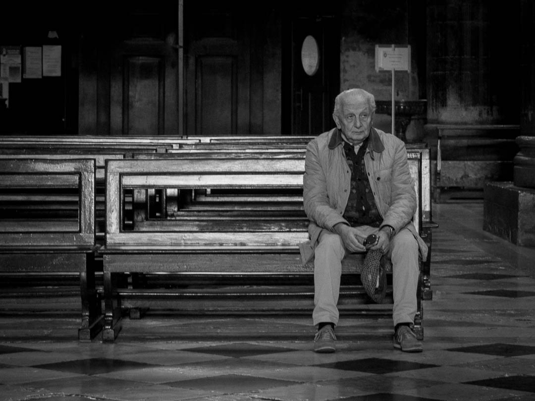 A man sits alone in a church in Cremona, Italy