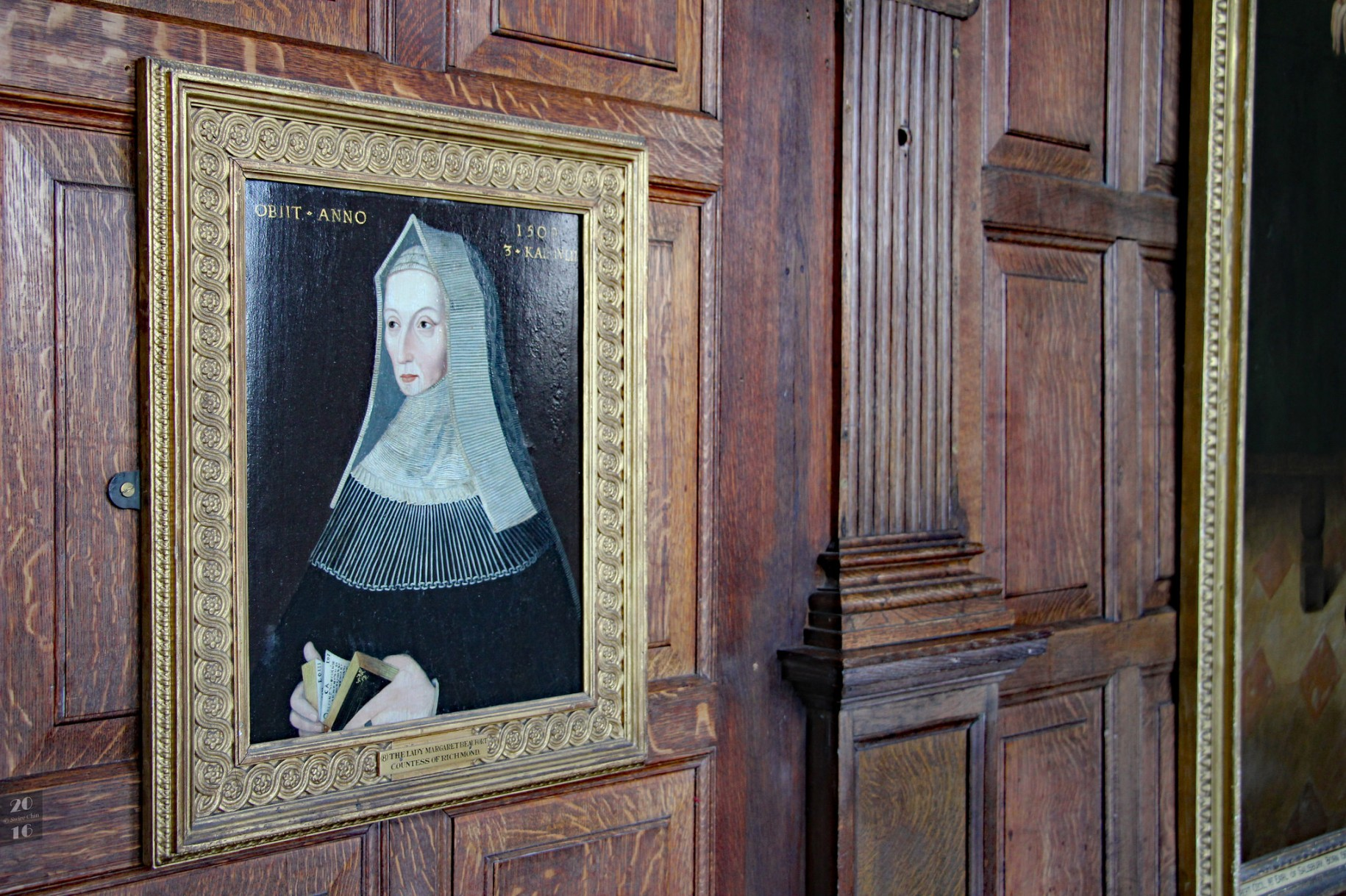 A portrait of a white woman wearing a black dress and white veil hangs on a wall covered with dark wood panels